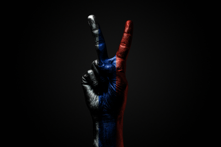 A hand with a drawn Russia flag shows an PEACE sign, a symbol of peace, friendship, greetings and peacefulness on a dark background. Horizontal frame Stockfoto