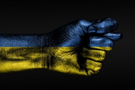 A hand with a painted Ukraine flag shows a fig, a sign of aggression, disagreement, a dispute on a dark background. Horizontal frame