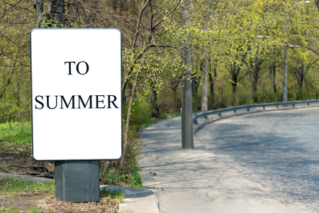 Vertical billboard with an inscription on a white background IN SUMMER, stands on the side of the road from the bricks