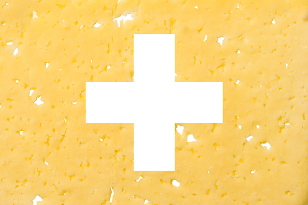 Switzerland flag cut out of cheese, as a symbol of the import or export of cheese on a white isolated background. Horizontal frame Stockfoto