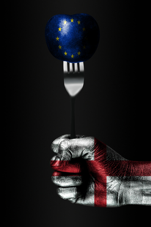 A hand with a drawn England flag holds a fork, on which is a ball with a drawn EU flag, a sign of influence, pressure, grip and anecxia. Vertical frame Stockfoto