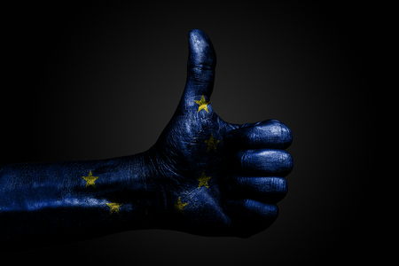A hand with a drawn EU flag shows a finger up sign, a symbol of success, readiness, a task done on a dark background. Vertical frame Stockfoto