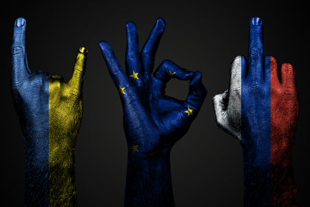 a set of three hands with a painted flag of Ukraine, Russia and the European Union show middle finger, goat and Okay, a sign of aggression, protest and approval on a dark background. Horizontal frame