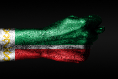 A hand with a painted Chechnya flag shows a fig, a sign of aggression, disagreement, a dispute on a dark background. Horizontal frame