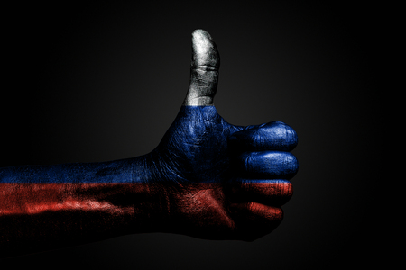 A hand with a drawn Russia flag shows a finger up sign, a symbol of success, readiness, a task done on a dark background. Vertical frame