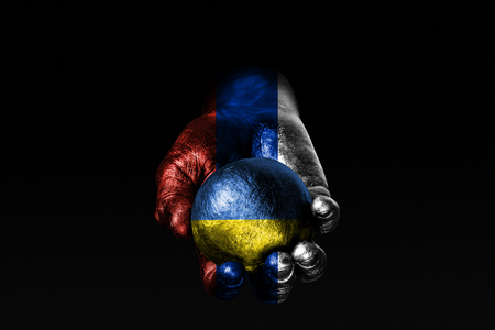 A hand with a drawn Russia flag holds a ball with a drawn Ukraine flag, a sign of influence, pressure or conservation and protection. Horizontal frame