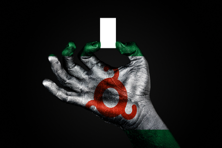 hand with a painted flag Ingushetia holding a small white sheet with space for an inscription, mock up. Horizontal frame