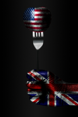 A hand with a drawn Great Britain flag holds a fork, on which is a ball with a drawn USA flag, a sign of influence, pressure, grip and anecxia. Vertical frame