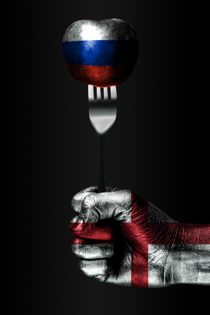 A hand with a drawn England flag holds a fork, on which is a ball with a drawn Russia flag, a sign of influence, pressure, grip and anorexia. Vertical frame