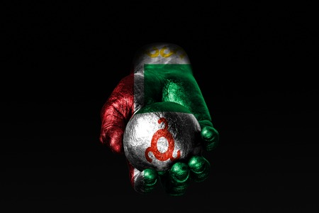 A hand with a drawn Chechnya flag holds a ball with a drawn Ingushetia flag, a sign of influence, pressure or conservation and protection. Horizontal frame Stockfoto