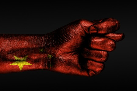 A hand with a painted China flag shows a fig, a sign of aggression, disagreement, a dispute on a dark background. Horizontal frame