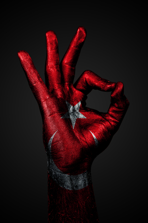 A hand with the painted flag of Turkey shows an OK sign on a dark background. Vertical frame