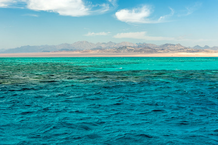 Seascape, view of the blue sea with high bald mountains in the background. Horizontal frame