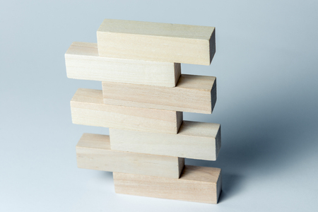 a pyramid of wooden cubes lying on top of each other with space for an inscription, on an uneven white background