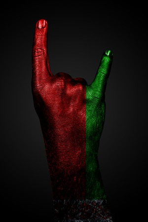 A hand with a drawn flag of Belarus shows a goat sign on a dark background. Vertical frame Stockfoto