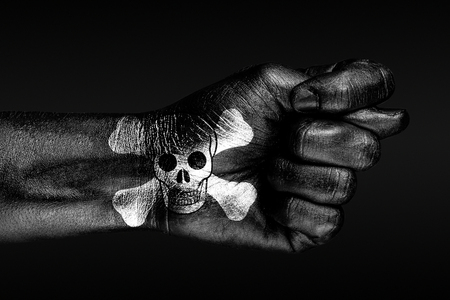 On a hand with a painted human skull and bones depicted a fig, a sign of aggression, disagreement, piracy, on a dark background. Horizontal frame Stockfoto