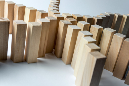 Many curved lines of wooden cubes are connected in the center into one, as a symbol of queues, a variety of tasks and a leader, on an uneven white background.