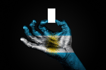 hand with a painted flag Argentina holding a small white sheet with space for an inscription, mock up. Horizontal frame Stockfoto