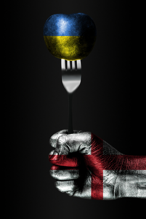 A hand with a drawn England flag holds a fork, on which is a ball with a drawn Ukraine flag, a sign of influence, pressure, grip and anecxia. Vertical frame