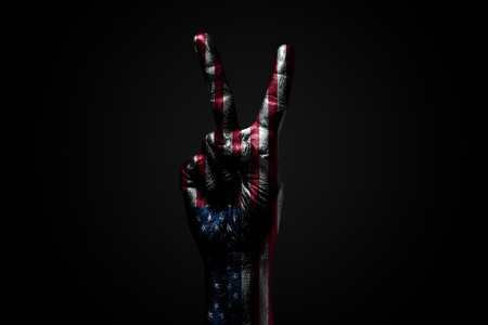 A hand with a drawn USA flag shows an PEACE sign, a symbol of peace, friendship, greetings and peacefulness on a dark background. Horizontal frame