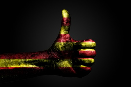 A hand with a drawn Catalonia flag shows a finger up sign, a symbol of success, readiness, a task done on a dark background. Vertical frame