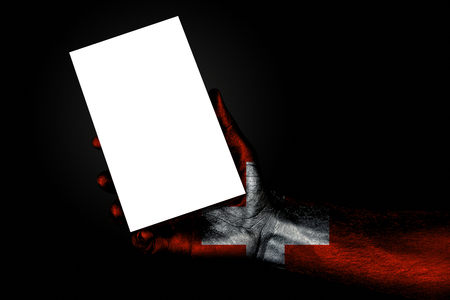 hand with painted flag Switzerland holding a large white sheet with space for an inscription, mock up. Horizontal frame