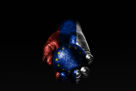A hand with a drawn Russia flag holds a ball with a drawn EU flag, a sign of influence, pressure or conservation and protection. Horizontal frame Stockfoto