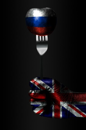 A hand with a drawn Great Britain flag holds a fork, on which is a ball with a drawn Russia flag, a sign of influence, pressure, grip and anecxia. Vertical frame