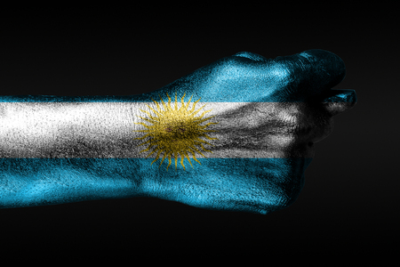 A hand with a painted Argentina flag shows a fig, a sign of aggression, disagreement, a dispute on a dark background. Horizontal frame