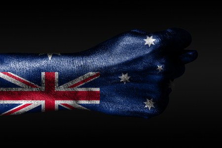 A hand with a painted Australia flag shows a fig, a sign of aggression, disagreement, a dispute on a dark background. Horizontal frame