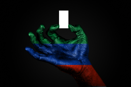 hand with a painted flag Dagestan holding a small white sheet with space for an inscription, mock up. Horizontal frame