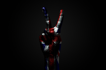 A hand with a drawn Great Britain flag shows an PEACE sign, a symbol of peace, friendship, greetings and peacefulness on a dark background. Horizontal frame Stockfoto