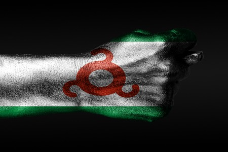 A hand with a painted Ingushetia flag shows a fig, a sign of aggression, disagreement, a dispute on a dark background. Horizontal frame