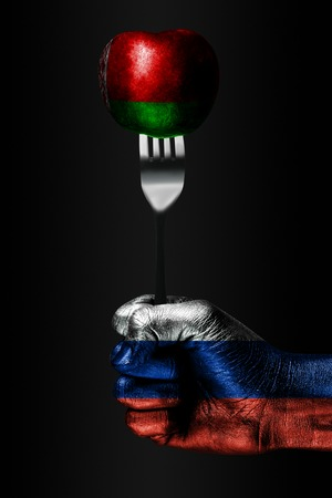 A hand with a drawn Russia flag holds a fork, on which is a ball with a drawn Belarus flag, a sign of influence, pressure, grip and anecxia. Vertical frame