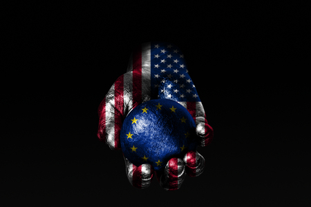 A hand with a drawn USA flag holds a ball with a drawn EU flag, a sign of influence, pressure or conservation and protection. Horizontal frame Stockfoto
