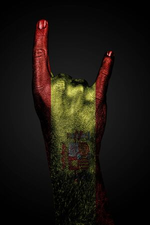 A hand with a drawn Spain flag shows a goat sign, a symbol of mainstream, metal and rock music, on a dark background. Vertical frame