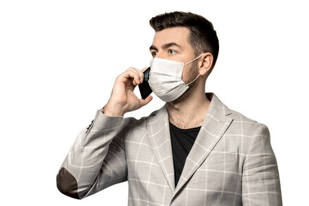 A young man in a white jacket, masked by a virus, speaks on a smartphone on a white background.