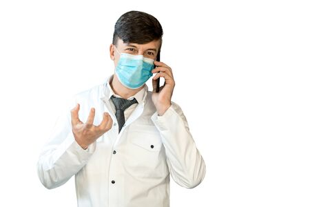A young doctor in a white coat and a virus mask is talking on the phone. 免版税图像