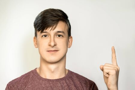 Portrait of a young man with dark hair, shows thumb up. Place for layout.