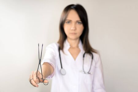 Young woman doctor with dark hair in a white medical coat, with a stethoscope and scissors. 免版税图像