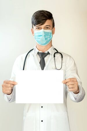 Theme of health and healthcare. A young doctor with dark hair is standing in a white coat and a mask from the virus, with a stethostop, holding a white sheet for mockup. 免版税图像