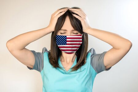 Theme of health and safety. A young female doctor with dark hair in a mask from a virus with the US flag, holds on his head.