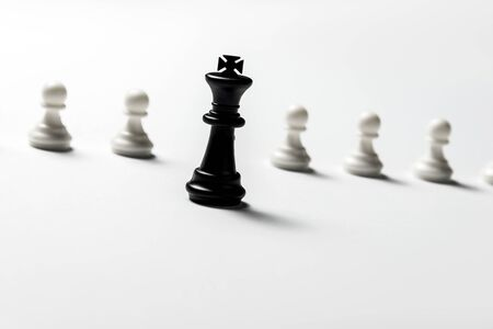 chess king is standing against white pawns. Symbol of leadership and confrontation. 免版税图像