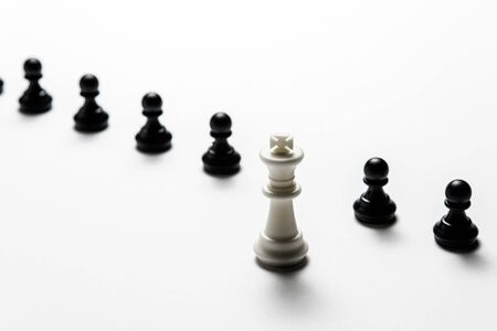 chess white king stands against black pawns. Symbol of leadership and confrontation.