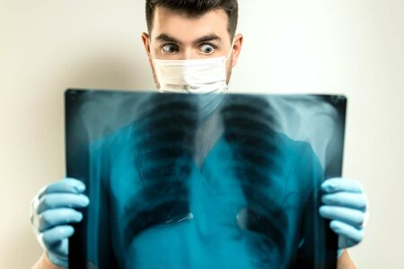 young male doctor in a mask from a virus, examines an x-ray.
