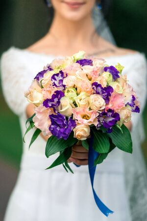 bride in a white dress with a beautiful bouquet, close-up. 免版税图像