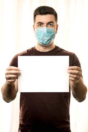 Theme of coronavirus and safety. A young man in a mask from a virus stands with a white sheet for a mockup, on a light background. 免版税图像