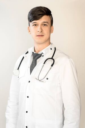Theme of health and healthcare. A young doctor with dark hair is standing in a white coat with a stethoscope on a light background. 免版税图像