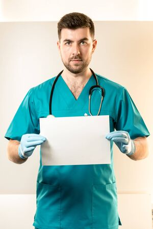 young male doctor holding a white sheet with place for mockup. 免版税图像
