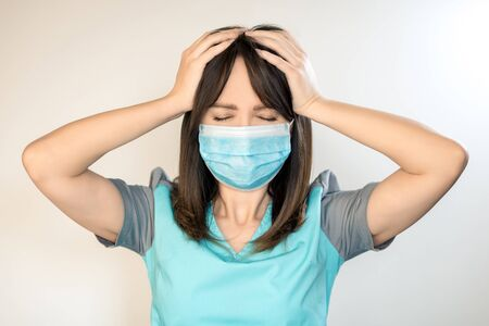 The topic of coronavirus and safety. A young female doctor with dark hair in a mask from a virus holds onto her head.